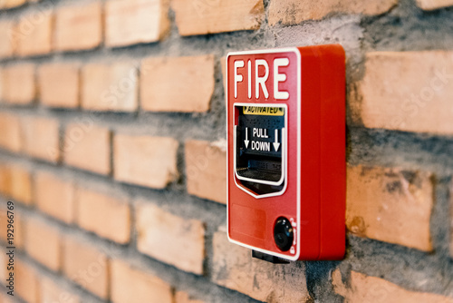 Photo Close up fire alarm activation box on brick wall in room