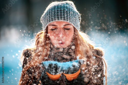 Photo Winter woman blowing snow outdoor at sunny day, flying snowflakes