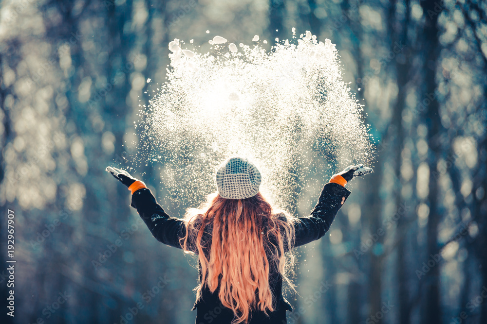 Fototapeta Young girl throwing snow in the air at sunny winter day, back view