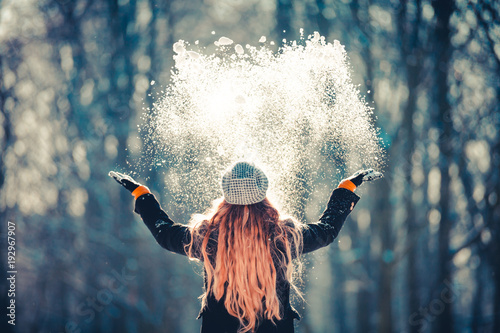 Fotografia Young girl throwing snow in the air at sunny winter day, back view