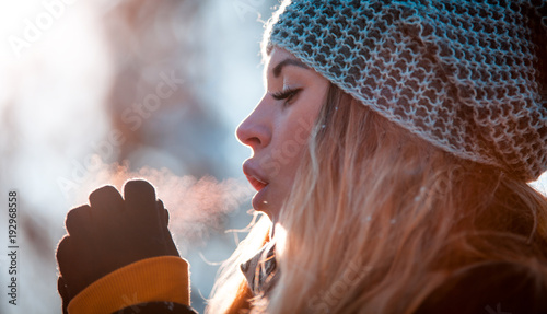 Fotografia, Obraz  Woman breathing on her hands to keep them warm in cold winter day