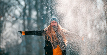 Smiling Woman Throwing Snow In...
