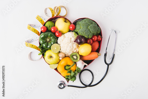 vegetables and fruits laying in heart shaped dish near stethoscope and measuring Fototapet