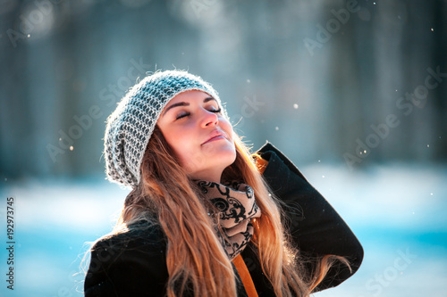 Fotografia  Young woman walking in winter park at sunny day