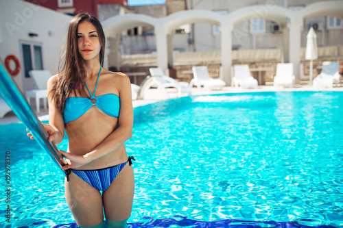 Fit woman in the bikini getting into the pool Using hotel