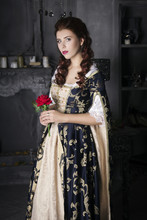 Beautiful Woman In An Old Dress With A Train And A Rose In His Hand. Vintage Furnishings, Historic Vintage Image. The Girl With White Skin, Red Lips And Beautiful Wavy Hair. Portrait Photo.