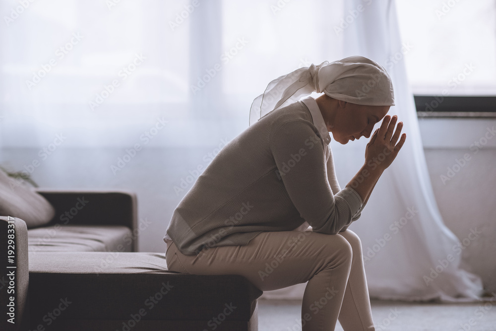 Fototapeta side view of upset sick mature woman in kerchief sitting at home, cancer concept