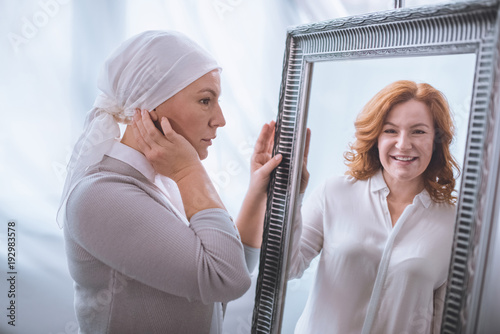 Fotografering upset sick mature woman in kerchief looking at smiling reflection in mirror, can