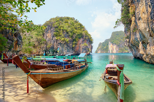 Beautiful landscape with traditional longtail boats, rocks, cliffs, tropical beach. Krabi, Thailand.