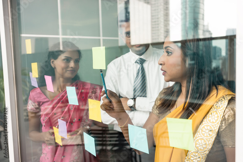 Fototapeta Three Indian employees sticking reminders on glass wall with business tasks and