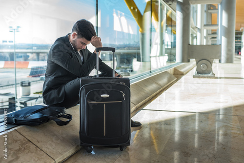 Fototapeta young businessman upset at the airport waiting his delayed flight with luggage obraz