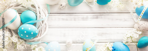 Fotografia Easter Decoration with Eggs and Flowers on White Wooden Background
