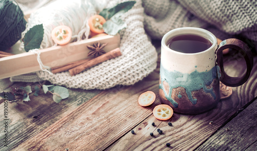 still life a cozy cup of tea with kumquat on a wooden background, the concept of coziness and pastime