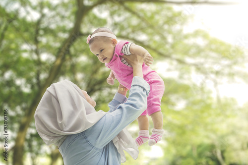 Fotografie, Obraz  Muslim mother playing with daughter at park