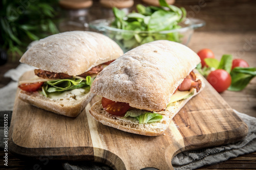 Staande foto Snack Ciabatta sandwich with arugula salad, bacon and yellow cheese.