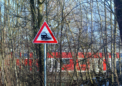 Fotografia, Obraz  railroad level crossing sign on rural road and train traveling across