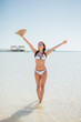Summer vacation happiness carefree joyful sun hat woman with open arms in success enjoying tropical beach destination. Holiday bikini girl relaxing on sea beach
