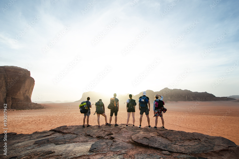 Tourist friends on a top of mountains in a desert. Sunset view. Nature. Tourist people enjoy a moment in a nature. Wadi rum national park - Jordan