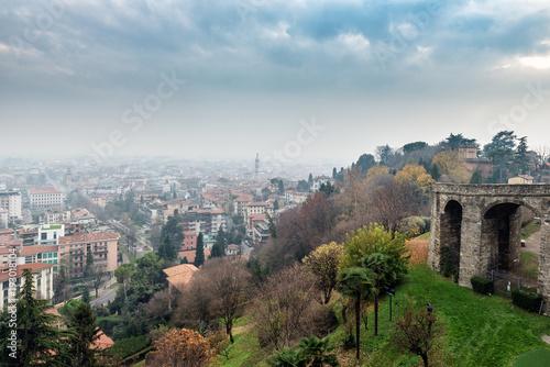 Plakat Powietrzny panoramiczny widok na mgłowym Bergamo miasteczku w północnym Włochy