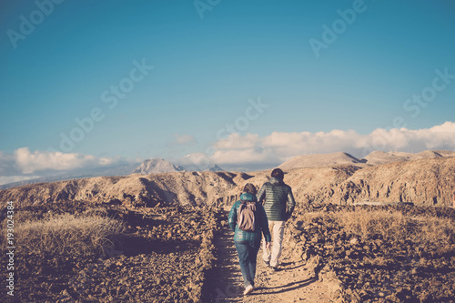 Senior mother and 45 year old son spend time together walking on an isolated pat Canvas Print