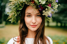 Closeup Portrait Of Beautiful Young Girl In Traditional Slavic Dress With Wreath Of Summer Flowers. Ethno Folk Style Cheerful Female On Abstract Background In Summer At Floral Feast. Expressive Face.