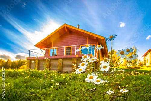 Cottage in the background of a summer day. Wooden cottage. Flowers on the background of the house. Private house with balcony.