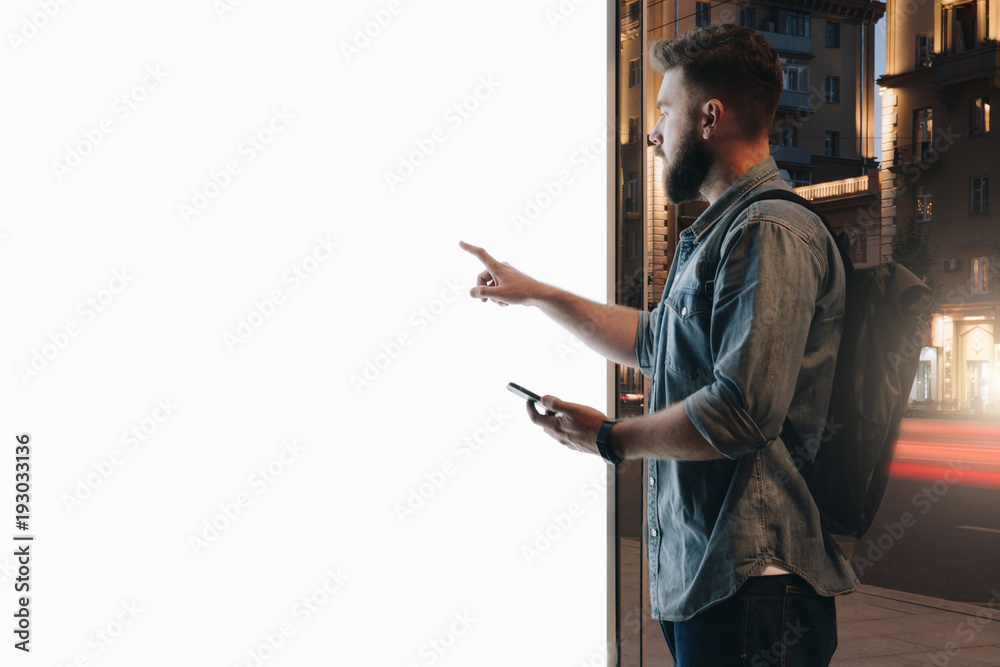 Fototapety, obrazy: Summer night. Young hipster bearded man stands on city street and touches large glowing touchscreen while holding smartphone. Innovative technologies, digital display, urban navigation. Mock up.