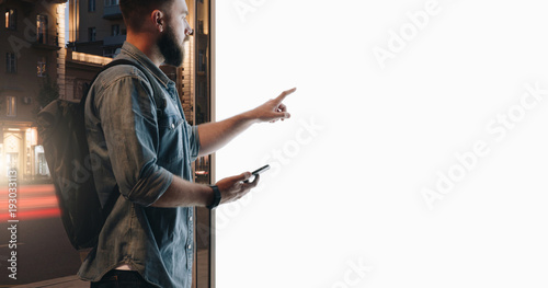 Fototapeta Summer night. Young hipster bearded man stands on city street and touches large glowing touchscreen while holding smartphone. Innovative technologies, digital display, urban navigation. Mock up. obraz