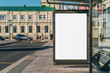 canvas print picture Vertical blank white billboard at bus stop on city street. In the background buildings and road. Mock up. Poster on street next to roadway. Sunny summer day.
