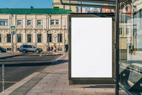 Fotobehang Historisch geb. Vertical blank white billboard at bus stop on city street. In the background buildings and road. Mock up. Poster on street next to roadway. Sunny summer day.