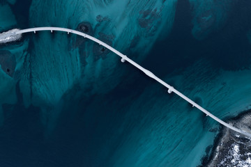 Aerial shot of a bridge over sea strait. Visible depth with blue and green colours near Tromso. Sommaroy, Norway