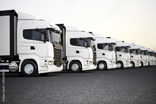 Fototapeta Fleet of white commercial transportation trucks parked in a row ready for business distribution