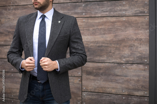 Fotografie, Obraz  Man in tailored suit standing and posing outdoors in front of wooden background