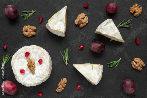 composition of camembert or brie cheese with grapes, walnuts, pomegranate and of rosemary
