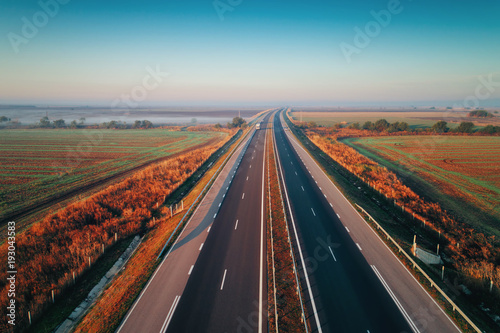 Foto op Aluminium Nacht snelweg Aerial view of highway with forest and fields in fog