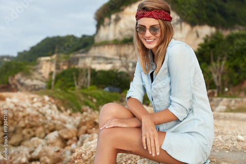 Photo Outdoor shot of pretty female wears sunglasses, red headband and loose t shirt, looks happily down, sits at cliff or in mountains, breezes fresh air and admires beautiful landscapes outside