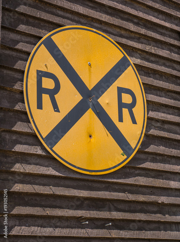Yellow And Black Railroad Crossing Sign On Brown Wooden Wall