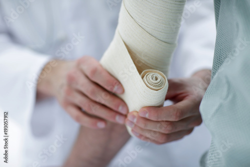 Photo closeup.doctor applying elastic bandage