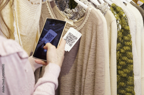 Valokuva  Woman scanning a QR code, with her smart phone, from a label in a clothing store