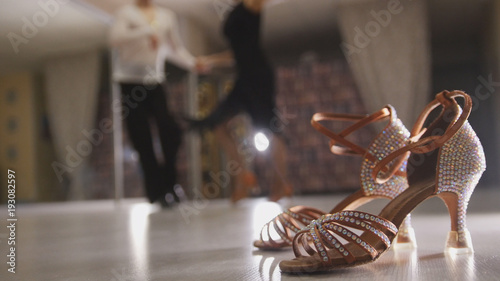Fototapeten Tanzschule Blurred professional man and woman dancing Latin dance in costumes in the Studio, ballroom shoes in the foreground