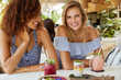 canvas print picture - Horizontal shot of females best friends with broad smile sit together at cafe table, share impressions about summer holidays, drink tasty smoothie and eat exotic dish. People, lifestyle, friendship
