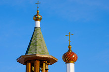 Two Towers Of An Orthodox Church With Crosses On The Tops, Gold Upholstery Against The Blue Sky