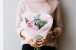 canvas print picture - Young woman holding a small beautiful blossoming peonies flower bouquet on the grey wall background, cropped photo