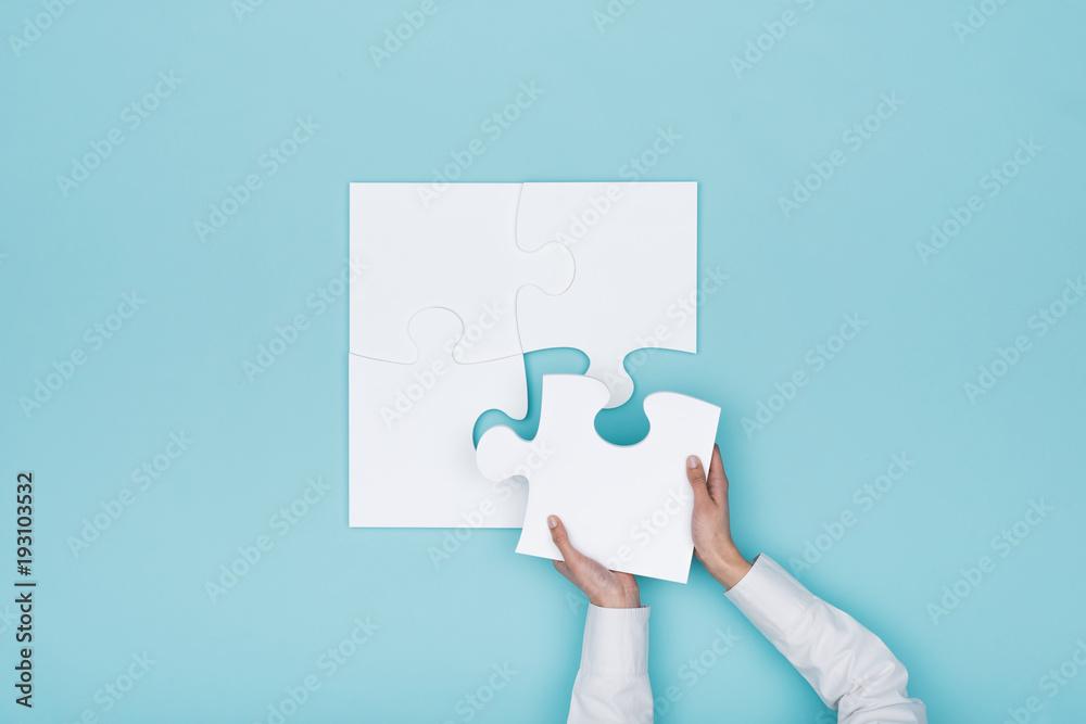 Fototapeta Woman assembling a jigsaw puzzle