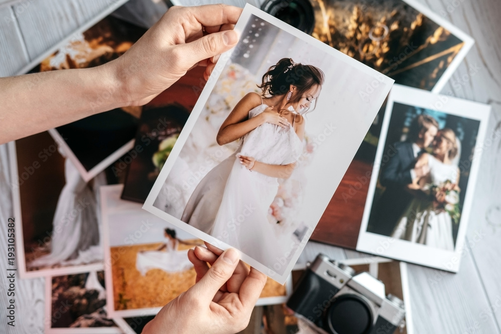 Fototapeta Printed wedding photos with the bride and groom, a vintage black camera and woman hands with photo - obraz na płótnie