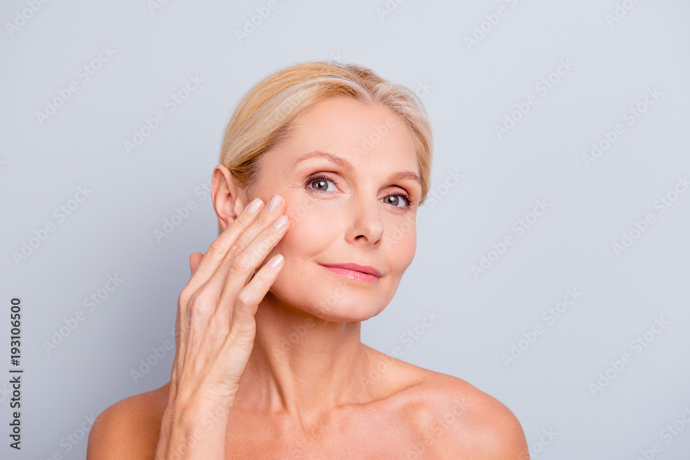 Fototapeta Pretty, charming, attractive woman touching, enjoying her perfect face skin, holding fingers on cheek, pimple, whelk, pustule, dry, oiled, problem skin concept, isolated on grey background