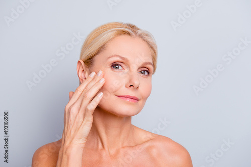 Obraz Pretty, charming, attractive woman touching, enjoying her perfect face skin, holding fingers on cheek, pimple, whelk, pustule, dry, oiled, problem skin concept, isolated on grey background - fototapety do salonu