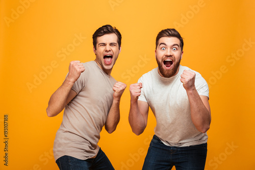 Fotografiet  Portrait of a two cheerful young men celebrating