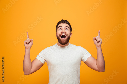 Photo  Portrait of a happy bearded man pointing fingers up