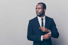 Portrait Of Stunning, Trendy, Attractive, Dreamy, Perfect Man In Black Suit With Tie Fasten Button On Sleeve Cuffs Of White Shirt, Looking To The Side, Isolated On Grey Background